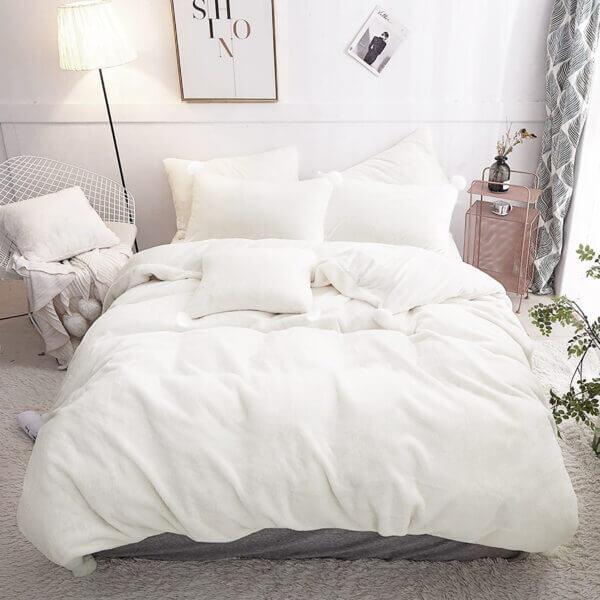 Duvet térmico en piel de durazno blanco con pompones blancos
